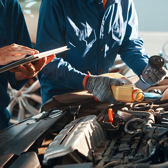 Mechanic adding oil to a car engine to promote Howard Insurance Brokers - Motor Trade Insurance